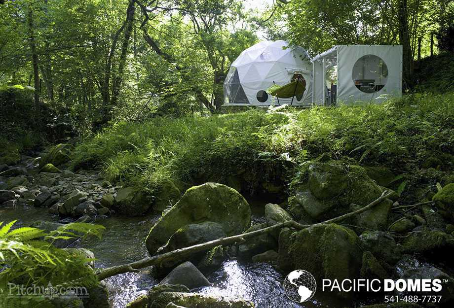 glamping dome tent next to a babbling brook