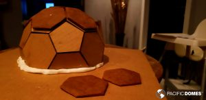 Our gingerbread trio affix the baked gingerbread shapes to the geodesic dome mold using the homemade frosting.